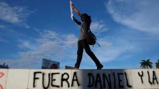 """Un manifestante se para encima de un muro marcado """"Fuera Daniel"""" durante una protesta en la cuidad de Managua el 18 de mayo."""