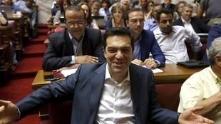 Greek Prime Minister Alexis Tsipras smiles before a ruling Syriza party parliamentary group session in Athens, Greece, 15 July 2015.