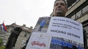 """The father of one of the accused Belgrade killers defends his son in court with a sign """"We want the truth"""", in April 2010"""