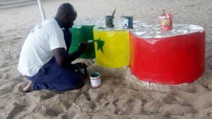 Bocar Ndiaye peint des bancs dans la cour de récréation de l'école Keur Ndiaye Lô de Rufisque.