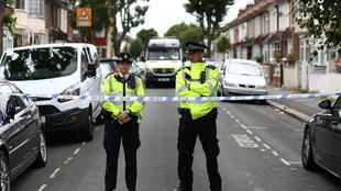 Police officers stand at a road block near a property in East Ham, east London on June 5, 2017.