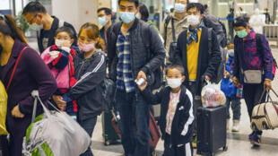 Unos trabajadores migrantes y sus familias hacen fila para abordar un tren y marcharse a Shenzhen, el 23 de marzo de 2020 en Yichang, en la provincia china de Hubei