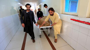 An injured man is transported on a stretcher in a hospital, after blasts at sports stadium, in Jalalabad