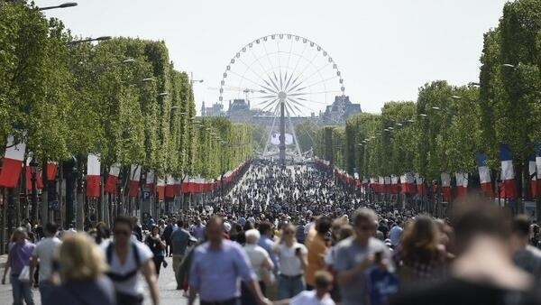 People walk along the Champs-Elysees Avenue in Paris, on May 8, 2016, as French capital's most famous avenue goes car-free for a day.