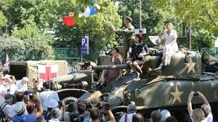 Crowds admire ethusiasts dressed up as 1940s Parisians and a US GI.