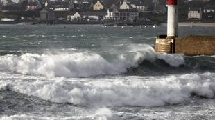 Waves roll in past a lighthouse, Brittany's Atlantic coast at  Audierne, France