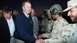 L'ex-président George H.W. Bush rencontre des soldats koweïtiens lors d'un exercice militaire près de la frontière irako-koweïtienne, lors de la fête nationale koweïtienne et dix ans après la libération de l'occupation irakienne, le 25 février 2001.