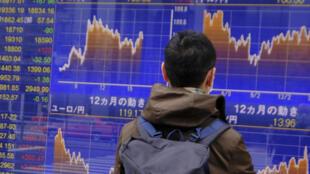 Un hombre sigue en una pantalla la tasa de cambio de la moneda extranjera frente al dólar el 31 de marzo de 2020 en Tokio