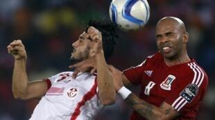 Equatorial Guinea's Iban Iyanga (R) beats Tunisia's Ferjani Sassi to the ball