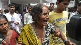 Avó chora na Índia após morte de neto intoxicado pela merenda escolar.