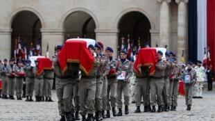 Les cercueils des 13 soldats français morts au Mali quittent les Invalides après la cérémonie en leur honneur, ce lundi 2 décembre à Paris.