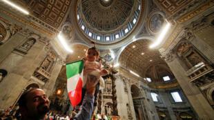 Мигрант с ребенком во время службы в соборе св. Петра в Риме, 14 января 2018 г.