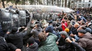 La police anti-émeute disperse des manifestants lors d'une manifestation contre le gouvernement réclamant des élections législatives anticipées à Tbilissi, en Géorgie, le 18 novembre 2019.