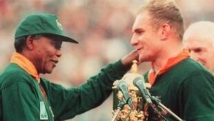 Nelson Mandela dando el Trofeo William Webb Ellis de la Copa del Mundo de Rugby a François Pienaar, el capitán del equipo sudafricano, el 24 de junio de 1995.