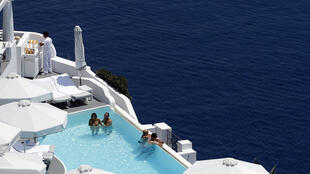Turistas relaxam em piscina de hotel na ilha de Santorini, na Grécia.