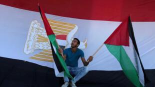 Na Faixa de Gaza, homem comemora acordo entre o Hamas e seu rival palestino, Fatah, na frente da bandeira egípcia, em 12 de outubro de 2017.