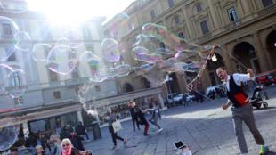 Các em nhỏ đang thổi chơi với bong bóng ở Piazza della Republica, thành phố Florence, Ý.