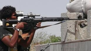 A member of the Southern Resistance Committees shoots at Houthi fighters in Aden 24 April 2015