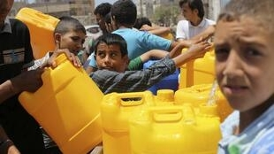 Em Khan Younes, no sul da Faixa de gaza, crianças palestinas aproveitam a trégua para encher galões com água.