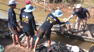 Allen Tan (right), the country head of the Golden West Humanitarian Foundation, greets the CMAC dive team prior to the mission.