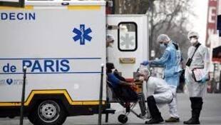 Врачи парижской скорой помощи забирают пациента с подозрением на коронавирус.