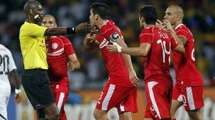 Tunisia's Karim Haggui (C) argues with referee Alioum Neant of Cameroon during their quarter-final soccer match against Ghana