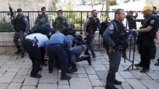 Palestino sendo preso por policiais israelenses em Jerusalém.