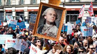 Манифестант в Париже несет портрет Эмманюэля Макрона в образе Людовика XIV. 5 мая 2018 г.