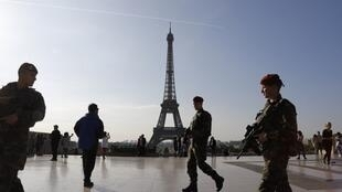 """French soldiers of the """"Operation Sentinelle"""" patrolling in front of the Eiffel tower in Paris."""