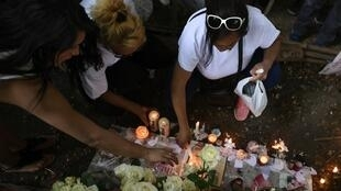 Demonstrators lay white roses and light candles at a makeshift memorial in tribute to Vanesa Campos