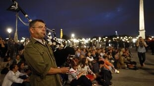 "A protester, who is part of the group ""Les Veilleurs"" (The Watchmen), blows a bagpipe during a demonstration against France's legalisation of same-sex marriage at Place de la Concorde in Paris 31 August 2013."