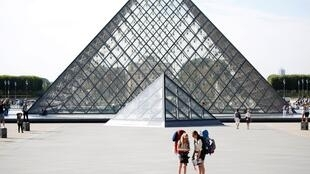 Turistas em frente à pirâmide do Louvre, projetada pelo arquiteto sino-americano Ieoh Ming Pei, em Paris.
