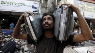 Homem carrega televisões estragadas no Paquistão.