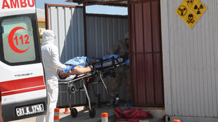 A Syrian man from Idlib is carried by Turkish medics wearing chemical protective suits to a hospital in the border town of Reyhanli in Hatay province on Tuesday.