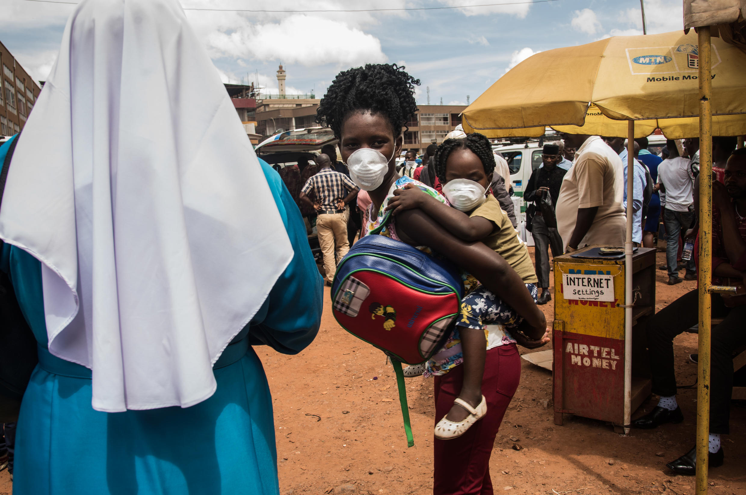 A mother and her child wear face masks as a preventive measure against Covid-19 at a bus park in Kampala, Uganda on 20 March 2020.