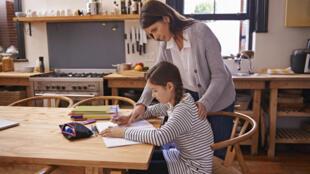 Une jeune femme aide sa fille à faire ses devoirs.