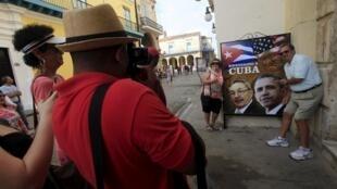 Des touristes californiens se prennent en photo près d'une affiche avec les présidents cubain Raul Castro et américain Barack Obama à la Havane, Cuba, le 19 mars 2016.