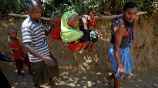 Một cụ bà 75 tuổi người Rohingya được người thân khiêng đi tị nạn sang Bangladesh.