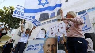 Les partisans du Premier ministre israélien Benyamin Netanyahu scandent des slogans et brandissent des pancartes pour le soutenir lors d'un contre-rassemblement devant le siège du Likoud dans la ville côtière méditerranéenne de Tel Aviv le 22 novembre 2019