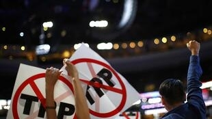 Delegates protesting against the Trans Pacific Partnership (TPP) trade agreement hold up signs during the first sesssion at the Democratic National Convention in Philadelphia, Pennsylvania, U.S. July 25, 2016.