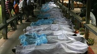 Relatives stand near bodies of stampede victims at a hospital in Phnom Penh