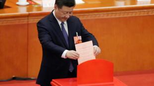O Presidente Xi Jinping participando no voto para a emenda constitucional, no Congresso da Assembleia Nacional Popular, em Beijing