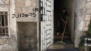A man clears away debris after an apartment housing Eritrean migrants was set on fire in Jerusalem, 4 June, 2012