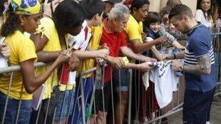 O jogador francês Matthieu Debuchy dá autógrafo em Ribeirão Preto, onde a seleção francesa está concentrada