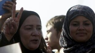 Samira Ibrahim (R) attends a protest against military council violations and virginity tests against females at Tahrir Square