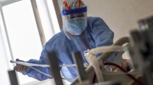 Un sanitario trata a un paciente infectado con coronavirus COVID-19 el 10 de marzo de 2020 en el Hospital de la Cruz Roja en Wuhan, China