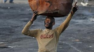 A township resident holds an old drum used as part of a barricade during protests