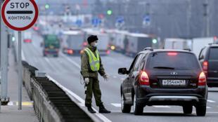 Policial verifica se motorista tem permissão para sair de casa em Moscou.