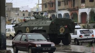 An armoured personnel carrier patrols the main square in Cite Ettadhamen near the capital Tunis