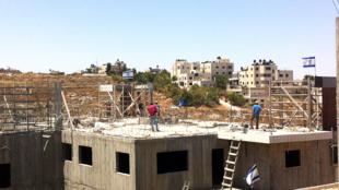 Des jeunes colons israéliens sur le toit d'un des deux bâtiments dont la Cour suprême israélienne a ordonné la destruction.